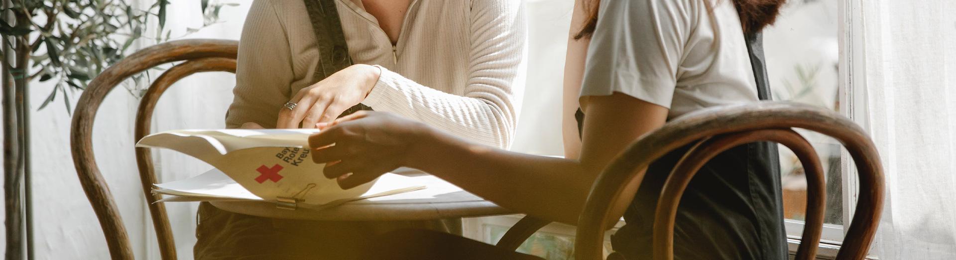 Zwei Frauen sehen sich Unterlagen an