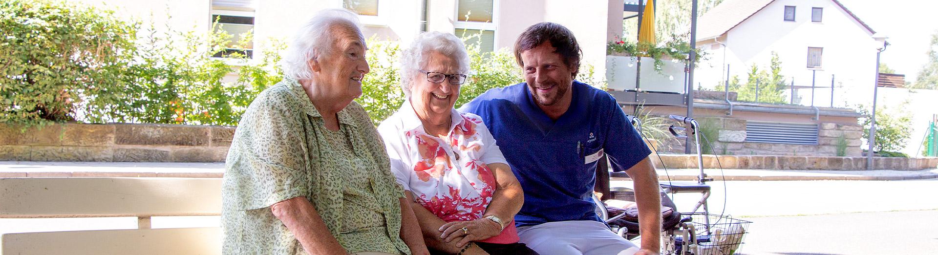 Pfleger und Bewonerinnen auf einer Parkbank bei einem Ausflug