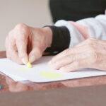 Hände einer Frau beim Malen mit Wachsmalstiften