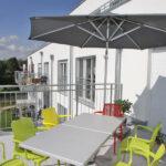 Terrasse mit Gartenstühlen und Sonnenschirm