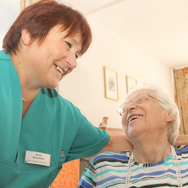 Pflegerin und Bewohnerin beim Lachen