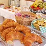 Frühstücksbuffett mit Hörnchen, Saft und frischem Obst