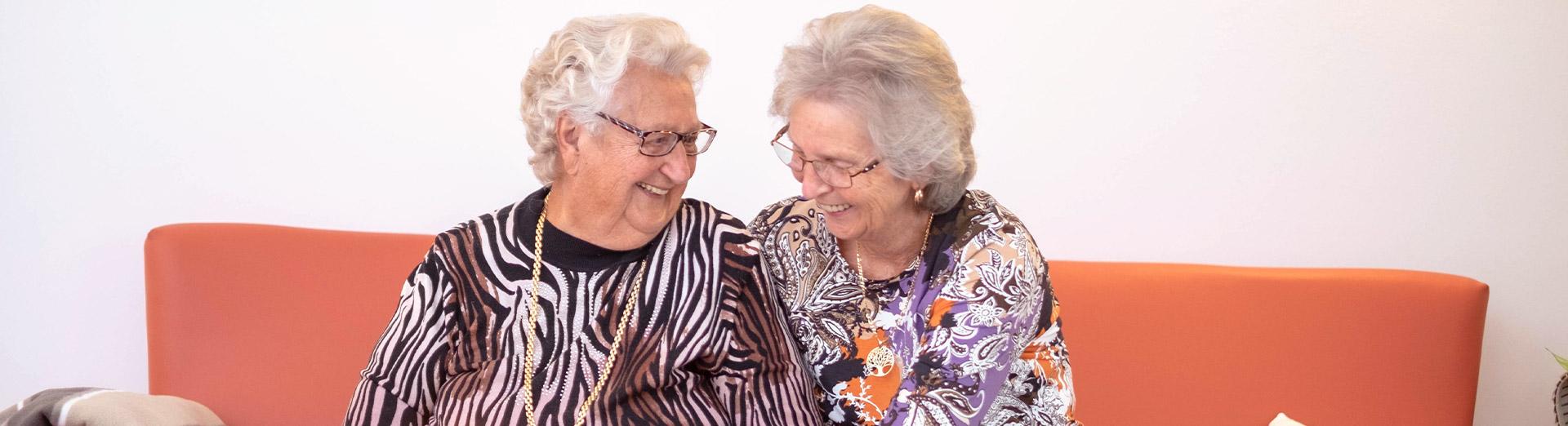 Zwei ältere, lachende Damen auf einer Couch